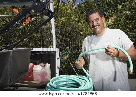Portrait of hispanic man holding water hose while standing in backyard