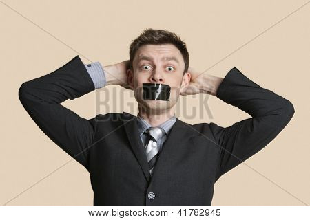 Portrait of a mid adult business professional staring with hands behind head and tape on mouth over colored background