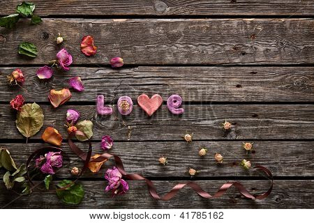 Sweet holiday background with word Love rose petals, curved ribbon on old wood.