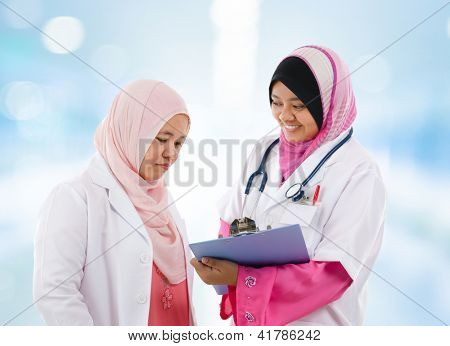 Two Southeast Asian Muslim medical doctor discussing on patient medical report, standing in hospital