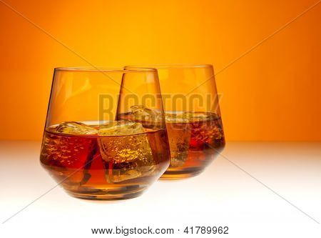Two tumblers filled with whisky on the rocks