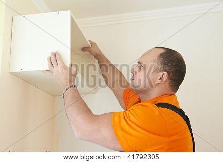 Craftsman carpenter at kitchen cabinet installation service work