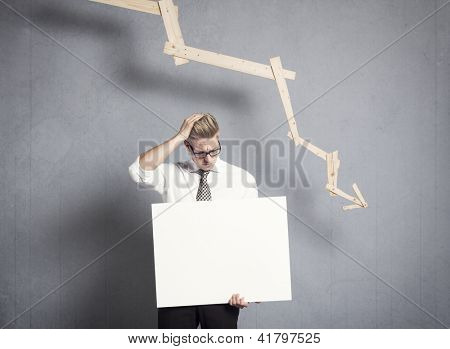 Concept: Business failure. Disappointed businessman presenting white empty signboard with space for text in front of business graph with negative trend, isolated on grey background.