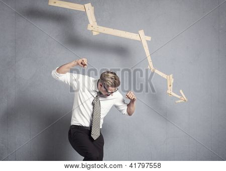 Concept: Business crash. Wrathful young businessman in front of business graph with negative trend, isolated on grey background.