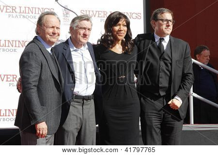 LOS ANGELES, CA - FEB 4: Billy Crystal, Robert De Niro, Grace Hightower, David O Russell as Robert De Niro gets with hand + foot prints at TCL Chinese Theater on February 4, 2013 in Los Angeles, CA