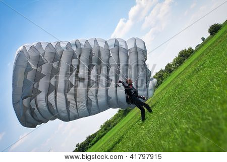 The parachutist under a white parachute against the blue sky