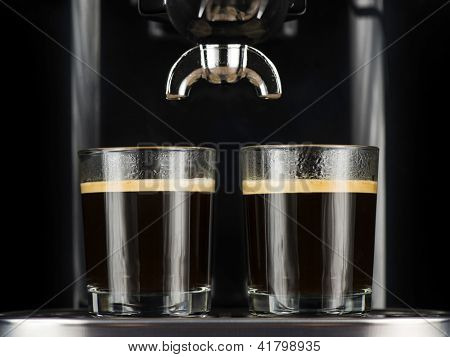 Two espresso cafes served in glasses under the percolator