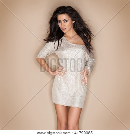 Stylish beautiful woman with long tousled brunette hair posing in a miniskirt  three quarter studio portrait on beige