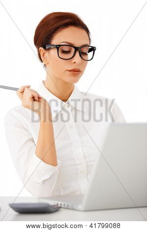 Elegant businesswoman seated at her desk wearing glasses reading her laptop screen with downcast eyes on a white background