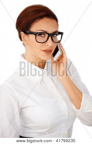 Attractive young brunette businesswoman in heavy framed glasses using a mobile phone isolated on white