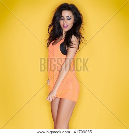 Sexy brunette woman in a skimpy shirt playfully trying to pull the hem to make it appear longer  posing on a yellow studio background