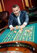 picture of gambler  - Joyful gambler stakes playing roulette at the casino - JPG