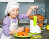 image of juicer  - little girl making carrot juice with a juice extractor - JPG