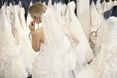 stock photo of bridal veil  - Back view of a young woman in wedding dress looking at bridal gowns on display in boutique - JPG