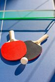 stock photo of ping pong  - table tennis ping pong two paddles and white ball on blue board - JPG