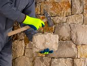 image of old stone fence  - stonecutter mason with hammer and stone building a masonry stone wall - JPG