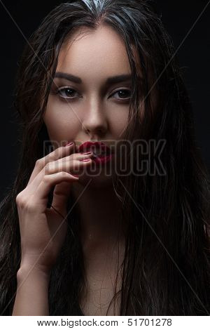 Fashion studio shot of young beautiful woman with red lipstick, red manicure and long wet hair