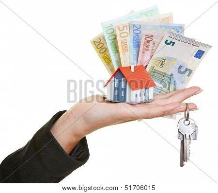Female hand holding little house, keys and Euro money bills