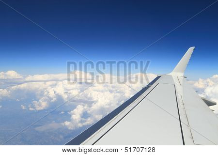 Blue horizon and huge clouds, aerial shot from airplane, with wing visible