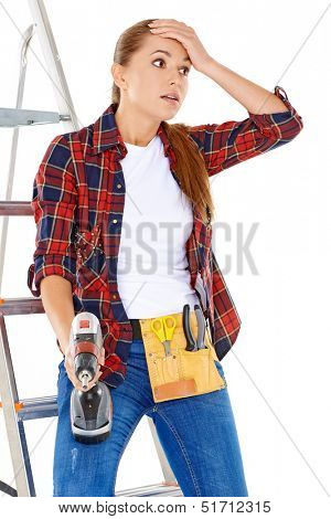 Worried DIY handy woman standing with her hand to her forehead and a wide eyed expression holding an electric drill and wearing a tool belt  isolated on white