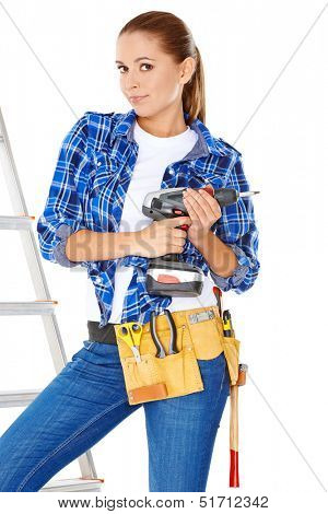 Confident happy DIY handy woman standing on a stepladder with a tool belt round her waist brandishing an electric drill in the air