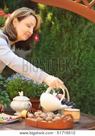 Woman Preparing Tea In Teapot In A Garden