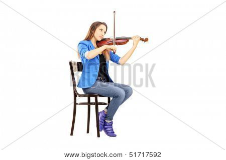 Casual young woman seated on a wooden chair playing the violin isolated on white background