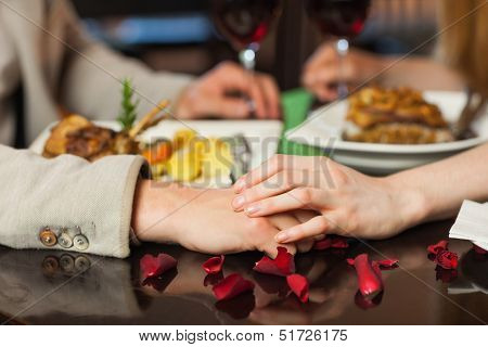 Close up on loving couple holding hands during romantic dinner