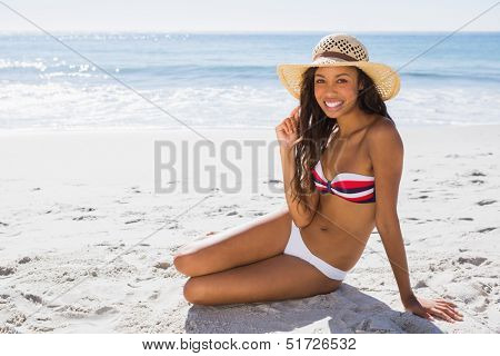 Smiling young tanned woman wearing straw hat posing on the beach