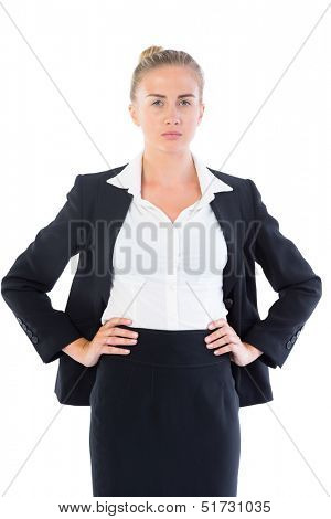 Serious young businesswoman posing with hands on hips on white background