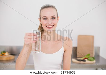 Happy young woman holding glass of water in the kitchen at home