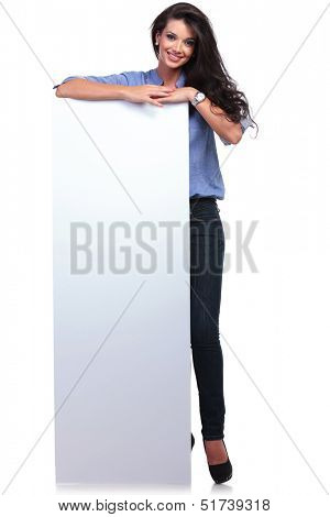full length picture of a young casual woman with an empty pannel smiling for the camera. on white background