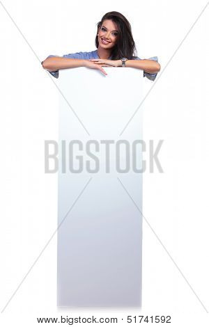 full length picture of a young casual woman standing behind an empty pannel and smiling for the camera. on white background