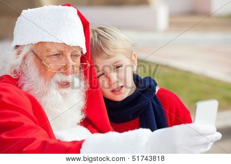 Santa Claus and boy taking selfportrait through smartphone in courtyard