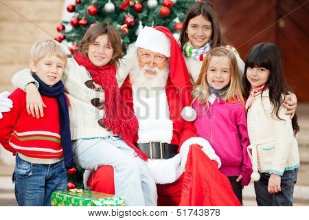 Portrait of happy Santa Claus and children outside house