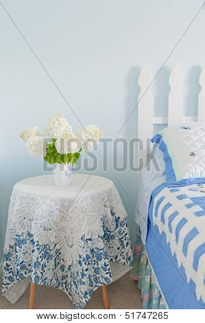 Bouquet Of White Hydrangea Flowers On A Side Bed Table In A Country Bedroom.