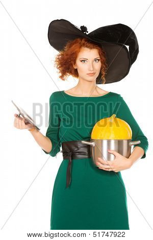 Charming red-haired witch holding a pan with pumpkin. Halloween. Isolated over white.