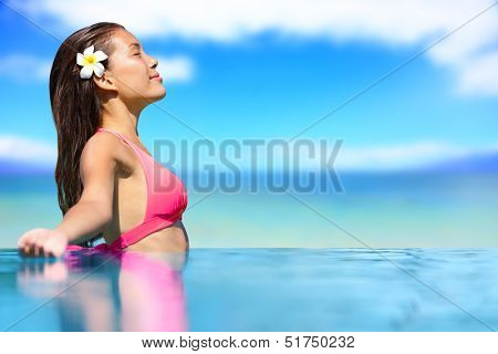 Spa vacation retreat woman relaxing at luxury travel resort. Happy blissful asian young woman in bikini in meditation enjoying summer sun and tanning during holidays on Hawaii.