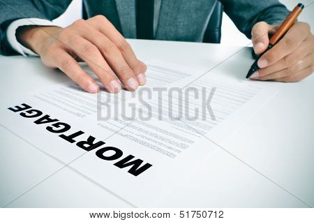 man wearing a suit sitting in a table signing mortgage loan contract
