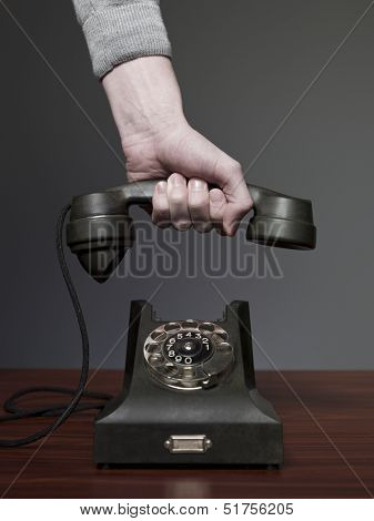 Man answering retro phone against a grey background