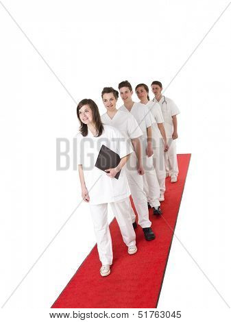 Doctor and Nurses on a red carpet isolated on white background