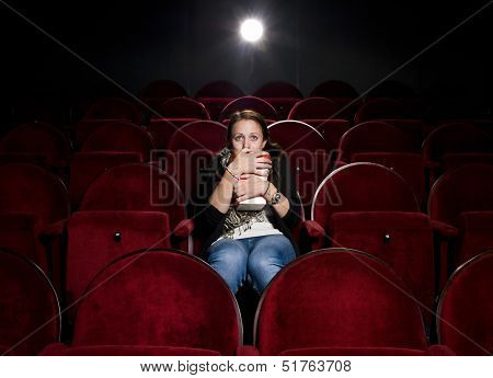 Afraid young woman alone in the movie theater