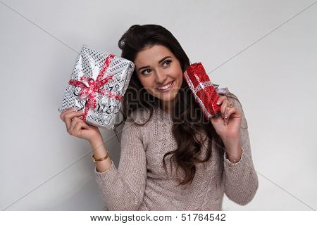 Beautiful girl with two christmas presents in beige sweater