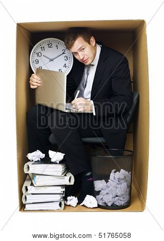 Businessman in a very tight office isolated on white background