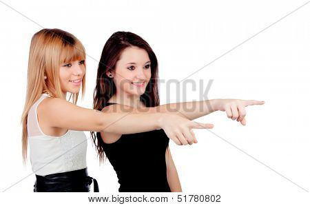 Two teen sisters pointing isolated on white background