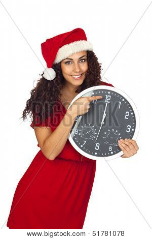 Pretty girl with christmas hat and a clock with twelve o'clock