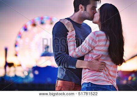 young couple kissing near santa monica pier