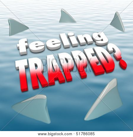 Feeling Trapped words on an ocean surrounded by shark fins to illustrate hopelessness, futility and fear of being attacked by your adversaries or enemies