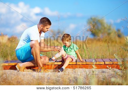 Father Bandaging Injured Leg Of Kid