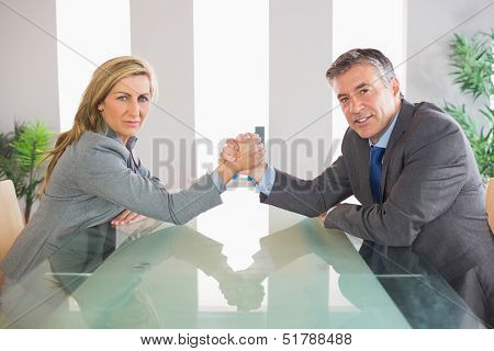 Two serious mature businesspeople having an arm wrestling sitting around a table at office
